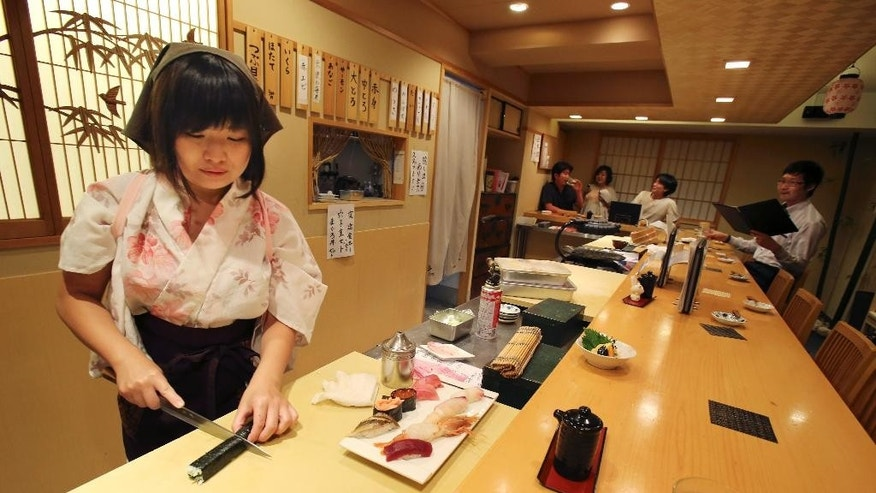 "In this Aug. 3, 2015 photo, Yuki Chidui, sushi chef and manager at Nadeshico sushi restaurant, cuts a cucumber roll to make a set of sushi at her all-women restaurant in Tokyo. Deeply rooted stereotypes such as the so-called ""Edo-style"" macho demeanor of sushi chefs and belief that warmer body temperature of women leads to inferior taste have kept sushi preparation an almost exclusively male domain in Japan. But some women are out to challenge tradition and are learning the art of sushi at a time when the government is emphasizing a greater role for women to offset Japan's shrinking workforce. (AP Photo/Koji Sasahara)"