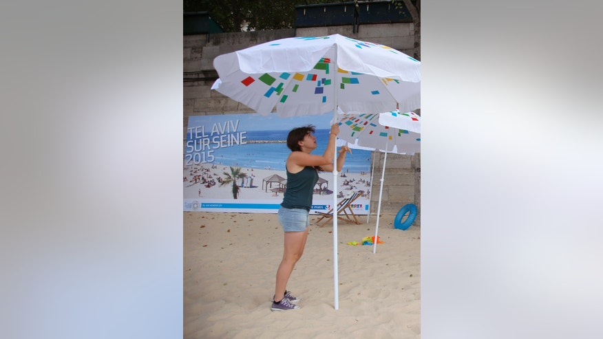 A volunteer installs a sun umbrella on the sand as part of the Paris Tel Aviv Beach on the banks of the Seine River in Paris, France, Thursday, Aug. 13, 2015. Paris is deploying hundreds of police to protect an urban beach event honoring Tel Aviv that has turned from a summertime celebration into a geopolitical hot potato. Leftist politicians and pro-Palestinian activists wanted it cancelled amid anger over a Jewish extremist attack that killed a toddler and his father in the West Bank. (AP Photo/Francois Mori)