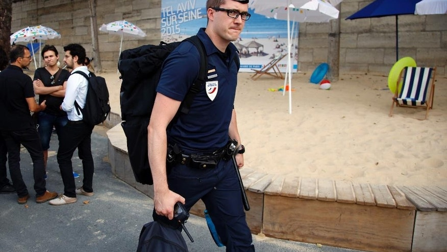 A French police officer arrives at the Paris Tel Aviv Beach on the banks of the Seine River in Paris, France, Thursday, Aug. 13, 2015. Paris is deploying hundreds of police to protect an urban beach event honoring Tel Aviv that has turned from a summertime celebration into a geopolitical hot potato. Leftist politicians and pro-Palestinian activists wanted it cancelled amid anger over a Jewish extremist attack that killed a toddler and his father in the West Bank. (AP Photo/Francois Mori)