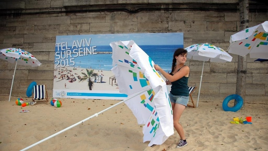 A volunteer installs a sun umbrella on the sand as part of the Paris Tel Aviv Beach on the banks of the Seine Rive in Paris, France, Thursday, Aug. 13, 2015. Paris is deploying hundreds of police to protect an urban beach event honoring Tel Aviv that has turned from a summertime celebration into a geopolitical hot potato. Leftist politicians and pro-Palestinian activists wanted it cancelled amid anger over a Jewish extremist attack that killed a toddler and his father in the West Bank. (AP Photo/Francois Mori)