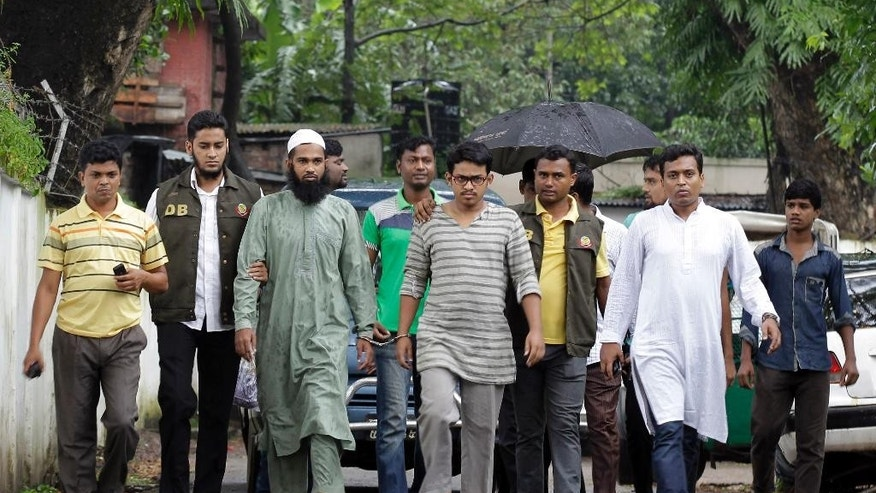 Suspected Muslim militants Saad-al-Nahin, foreground third right, and Masud Rana, third left, who were arrested in the last week's killing of a secular blogger, are escorted to appear before the media in Dhaka, Bangladesh, Friday, Aug. 14, 2015. Dhaka Metropolitan Police spokesman Muntasirul Islam said that the two, suspected members of Ansarullah Bangla Team, a group blamed for some of the previous attacks on bloggers, were arrested in the fourth such deadly attack this year Thursday evening by the detective branch, which has been handling the case rather than regular police. (AP Photo/A.M. Ahad)