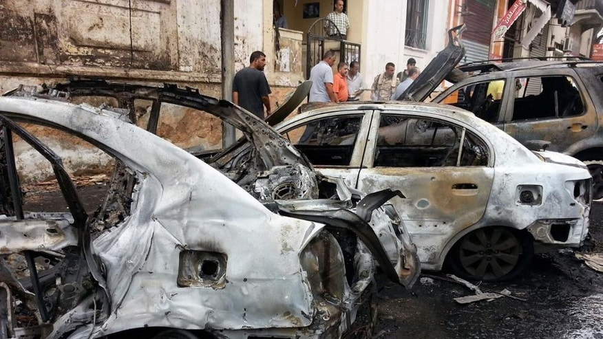 In this photo released by the Syrian official news agency SANA, Syrian men inspect cars that were burned by rockets that struck in the coastal city of Lattakia, Syria, Thursday, Aug. 13, 2015. Rockets fire struck several districts in the coastal city of Lattakia, a stronghold of Syrian President Bashar Assad, killing two civilians and wounding 13 others, the country's state-run news agency reported. (SANA via AP)