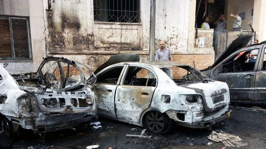 In this photo released by the Syrian official news agency SANA, a Syrian man inspects cars that were burned by rockets that struck in the coastal city of Lattakia, Syria, Thursday, Aug. 13, 2015. Rockets fire struck several districts in the coastal city of Lattakia, a stronghold of Syrian President Bashar Assad, killing two civilians and wounding 13 others, the country's state-run news agency reported. (SANA via AP)