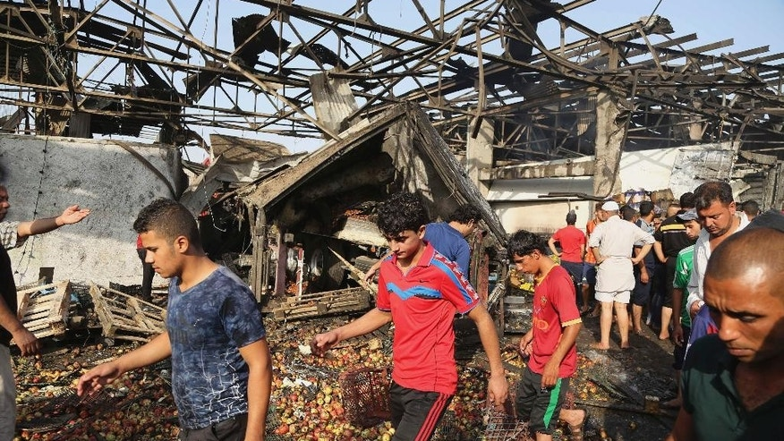 People gather at the scene of a truck bomb attack in Jameela market in the predominantly Shiite neighborhood of Sadr City, Baghdad, Iraq, Thursday, Aug. 13, 2015. The massive truck bomb ripped through the popular Baghdad food market in the Iraqi capital's crowded neighborhood in the early morning hours on Thursday, killing tens of people, police officials said, in one of the deadliest single blasts in the capital in years. (AP Photo/Karim Kadim)