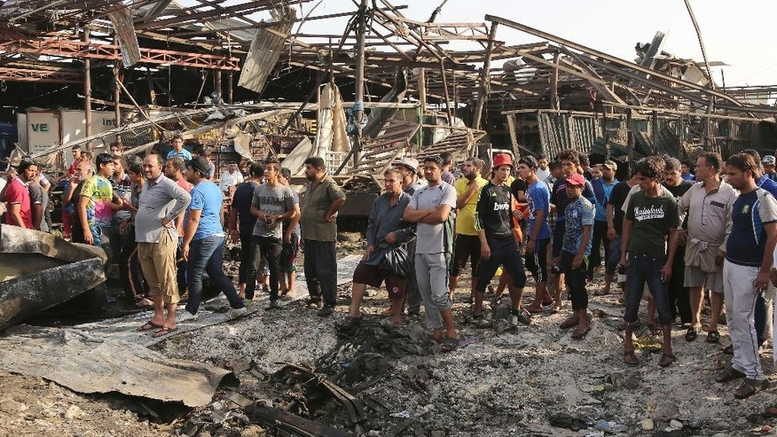 Civilians gather at the scene of a truck bomb attack in Jameela market in the predominantly Shiite neighborhood of Sadr City, Baghdad, Iraq, Thursday, Aug. 13, 2015. The massive truck bomb ripped through the popular Baghdad food market in the Iraqi capital's crowded neighborhood in the early morning hours on Thursday, killing tens of people, police officials said, in one of the deadliest single blasts in the capital in years. (AP Photo/Karim Kadim)