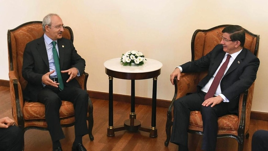 Turkish Prime Minister and leader of Justice and Development Party (AKP) Ahmet Davutoglu, right, talks with the main opposition Republican People's Party (CHP) Kemal Kilicdaroglu, prior to their meeting regarding possible coalition government between the two parties, in Ankara, Turkey, Thursday, Aug. 13, 2015. Davutoglu's Islamic-rooting ruling party lost its majority in elections in June, forcing it to seek a coalition alliance to remain in power.  But many in the ruling party favor new elections instead, and prospects for an alliance look dim and elections are likely to be called if no government is formed by the end of next week. (AP Photo)