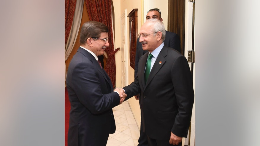 Turkish Prime Minister and leader of Justice and Development Party (AKP) Ahmet Davutoglu, left, shakes hands with the main opposition Republican People's Party (CHP) Kemal Kilicdaroglu, left, prior to their meeting regarding possible coalition government between the two parties, in Ankara, Turkey, Thursday, Aug. 13, 2015. Davutoglu's Islamic-rooting ruling party lost its majority in elections in June, forcing it to seek a coalition alliance to remain in power.  But many in the ruling party favor new elections instead, and prospects for an alliance look dim and elections are likely to be called if no government is formed by the end of next week. (AP Photo)