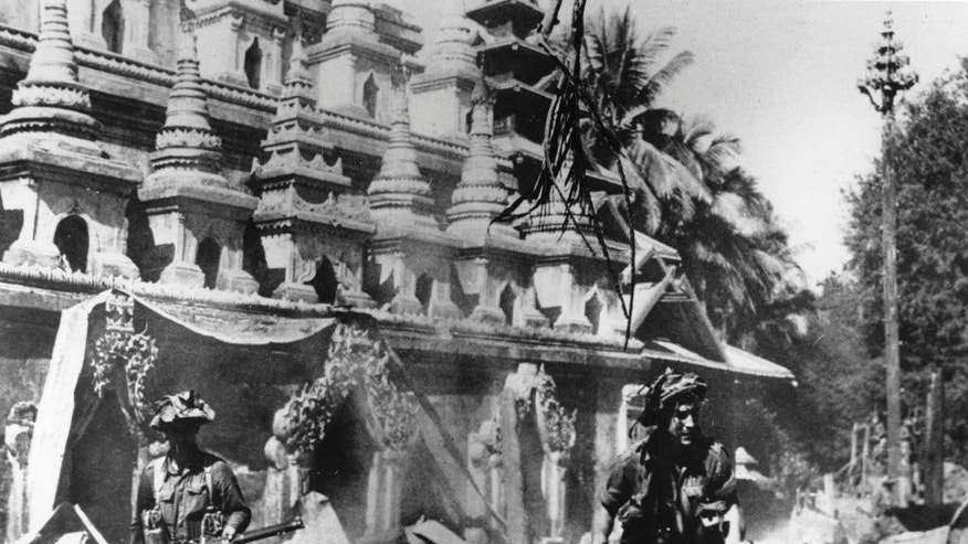 "FILE - In this January 26, 1945, file photo, men of the British 14th Army 36th Division pass a pagoda as they advance on a debris-littered street in an unknown Burmese town, during World War II. Seventy years after the war ended, withered and mostly impoverished veterans will gather at the graveside of a British officer who almost no one in England remembers. Maj. Hugh Paul Seagrim _ or ""Grandfather Longlegs"" _ remains a legend up in the hills of Myanmar, among a beleaguered ethnic minority for whom peace never came. (AP Photo, File)"