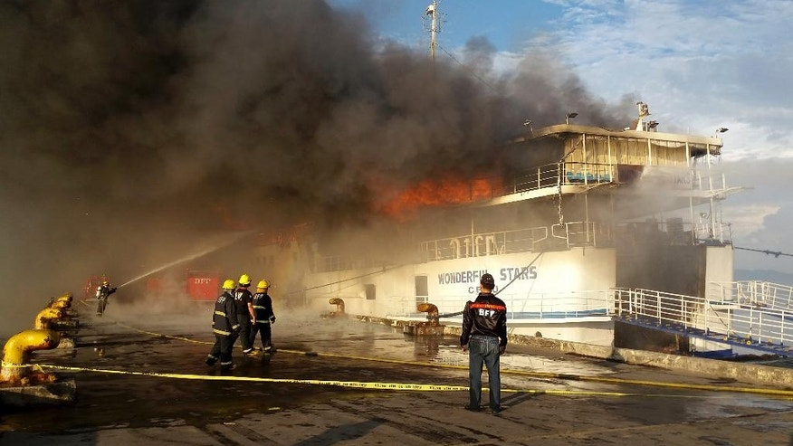 A fireman trains his hose at the burning MV Wonderful Stars ferry which caught fire at the port in Ormoc city in central Philippines early Saturday, Aug. 15, 2015. The inter-island ferry caught fire while it was docked and officials say all passengers have been safely evacuated. (AP Photo/John Kevin Pilapil)