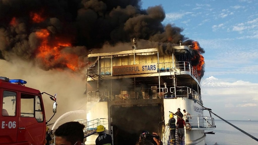 Black smoke rises from the burning MV Wonderful Stars ferry which caught fire at the port in Ormoc city in central Philippines early Saturday, Aug. 15, 2015. The inter-island ferry caught fire while it was docked and officials say all passengers have been safely evacuated. (AP Photo/John Kevin Pilapil)