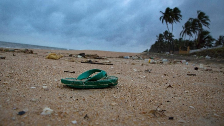 In this Aug. 13, 2015 photo, a sandal lies among other debris washed ashore on the Indian Ocean beach in Uswetakeiyawa, north of Colombo, Sri Lanka. For years along the Cornish coast of Britain, Atlantic Ocean currents have carried thousands of Lego pieces onto the beaches. In Kenya, cheap flip-flop sandals are churned relentlessly in the Indian Ocean surf, until finally being spit out onto the sand. In Bangladesh, fishermen are haunted by floating corpses that the Bay of Bengal sometimes puts in their path. And now, perhaps, the oceans have revealed something else: parts of Malaysian Airlines Flight 370, the jetliner that vanished 17 months ago with 239 people on board. (AP Photo/Gemunu Amarasinghe)