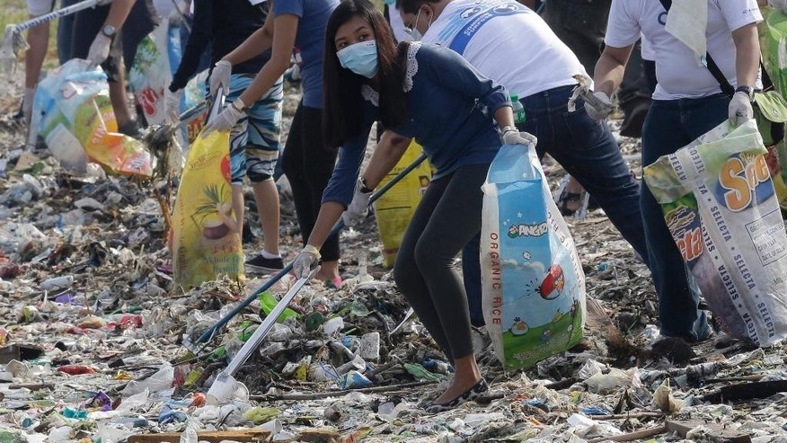 "FILE - In this June 8, 2013 file photo, volunteers and environmentalists remove dirt and garbage that were washed ashore at a bird sanctuary, known as ""Freedom Island,"" during a World Ocean Day event at Paranaque, south of Manila, Philippines. For years along the Cornish coast of Britain, Atlantic Ocean currents have carried thousands of Lego pieces onto the beaches. In Kenya, cheap flip-flop sandals are churned relentlessly in the Indian Ocean surf, until finally being spit out onto the sand. In Bangladesh, fishermen are haunted by floating corpses that the Bay of Bengal sometimes puts in their path. And now, perhaps, the oceans have revealed something else: parts of Malaysian Airlines Flight 370, the jetliner that vanished 17 months ago with 239 people on board. (AP Photo/Bullit Marquez, File)"