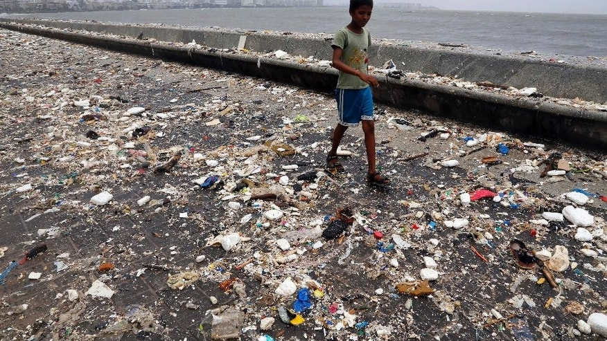 FILE- In this June 12, 2014 file photo, a boy walks through the Arabian Sea coast after tidal waves receded filling the shore with garbage in Mumbai, India. For years along the Cornish coast of Britain, Atlantic Ocean currents have carried thousands of Lego pieces onto the beaches. In Kenya, cheap flip-flop sandals are churned relentlessly in the Indian Ocean surf, until finally being spit out onto the sand. In Bangladesh, fishermen are haunted by floating corpses that the Bay of Bengal sometimes puts in their path. And now, perhaps, the oceans have revealed something else: parts of Malaysian Airlines Flight 370, the jetliner that vanished 17 months ago with 239 people on board. (AP Photo/Rajanish Kakade, File)