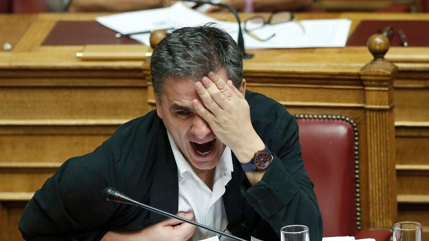 Greek Finance Minister Euclid Tsakalotos gestures during a parliamentary session in Athens, early Friday, Aug. 14, 2015. The Greek government defended its new bailout program in tumultuous parliamentary sessions as it faced a rebellion in the governing Syriza party ahead of a vote on the deal. (AP Photo/Yannis Liakos)