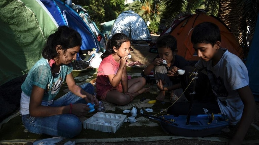 Migrants enjoy a drink at a park where hundreds of migrants are temporarily residing in Athens, Greece, Friday, Aug. 14, 2015. Greece is Europe's main gateway for refugees and economic migrants, after the alternative route from Libya to Italy became too dangerous. More than 130,000 people have reached the Greek islands this year - a 750 percent increase on 2014. (AP Photo/Giannis Papanikos)