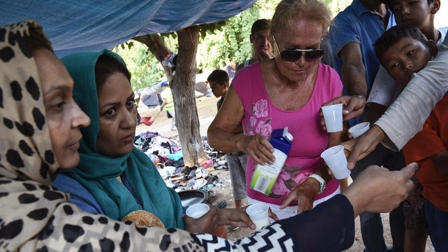 A volunteer delivers milk to migrants at a park where hundreds of migrants are temporarily residing in Athens, Greece, Friday, Aug. 14, 2015. Greece is Europe's main gateway for refugees and economic migrants, after the alternative route from Libya to Italy became too dangerous. More than 130,000 people have reached the Greek islands this year - a 750 percent increase on 2014.  (AP Photo/Giannis Papanikos)