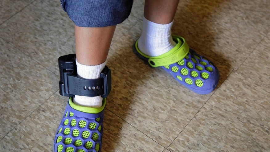 An immigrant from El Salvador wears an ankle monitor at a shelter, Monday, July 27, 2015, in San Antonio.
