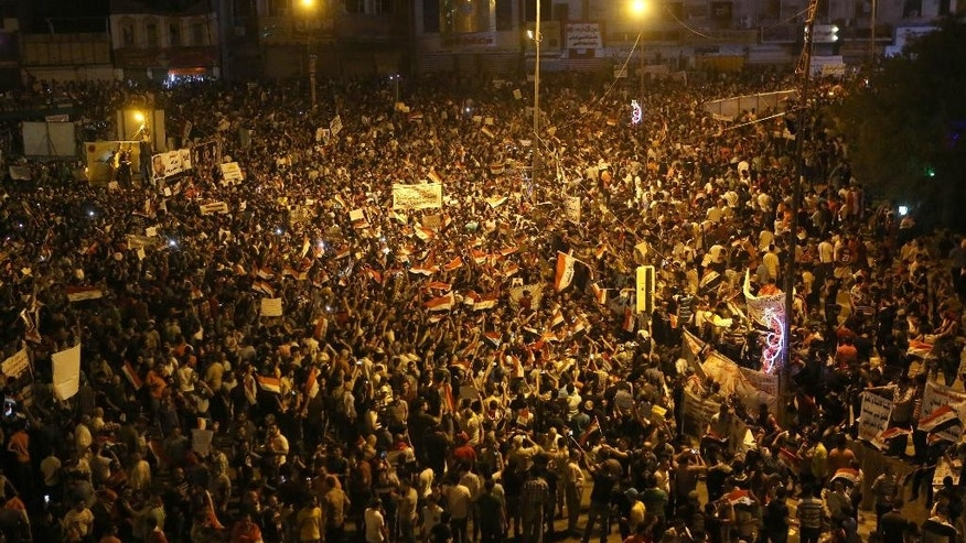 Protesters chant in support of Iraqi Prime Minister Haider al-Abadi as they wave national flags during a demonstration in Tahrir Square in Baghdad, Iraq, Friday, Aug. 14, 2015. Thousands of people demonstrated in cities across Iraq on Friday to show support for a reform plan put forth by the prime minister this week while still demanding that greater measures be taken to target corruption and restore basic services. (AP Photo/Khalid Mohammed)