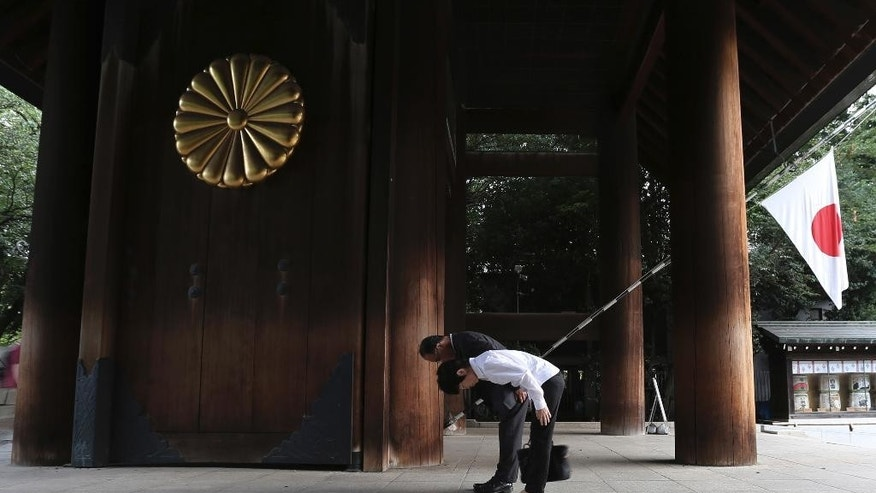 Visitors bow to pay respects to the war dead at Yasukuni Shrine in Tokyo Saturday, Aug. 15, 2015. Japan marked the 70th anniversary of the end of World War II. (AP Photo/Eugene Hoshiko)