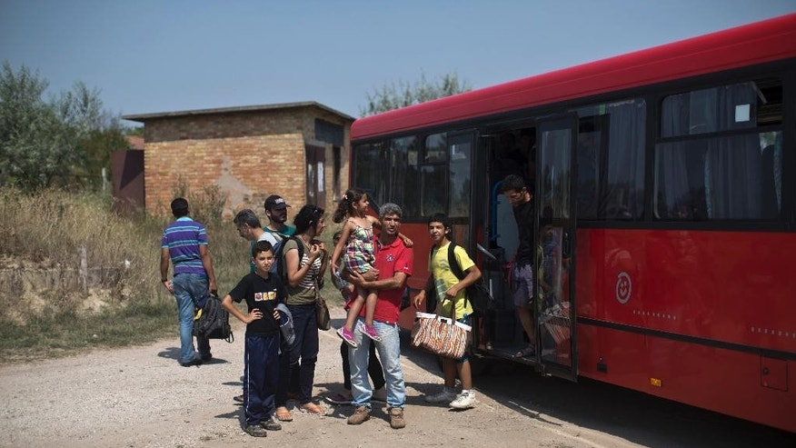 In this photo taken Wednesday, Aug. 12, 2015, migrants disembark a local bus in Kanjiza, Serbia. Serbia's border with EU-member Hungary has become a major crossing point for tens of thousands of migrants from the Middle East, Asia and Africa who are using the so-called Balkan route to enter the EU while fleeing poverty and wars in their home countries. (AP Photo/Marko Drobnjakovic)