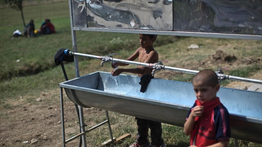 In this photo taken Wednesday, Aug. 12, 2015, a boy washes his shirt inside a camp for migrants in Kanjiza, Serbia. Serbia's border with EU-member Hungary has become a major crossing point for tens of thousands of migrants from the Middle East, Asia and Africa who are using the so-called Balkan route to enter the EU while fleeing poverty and wars in their home countries. (AP Photo/Marko Drobnjakovic)