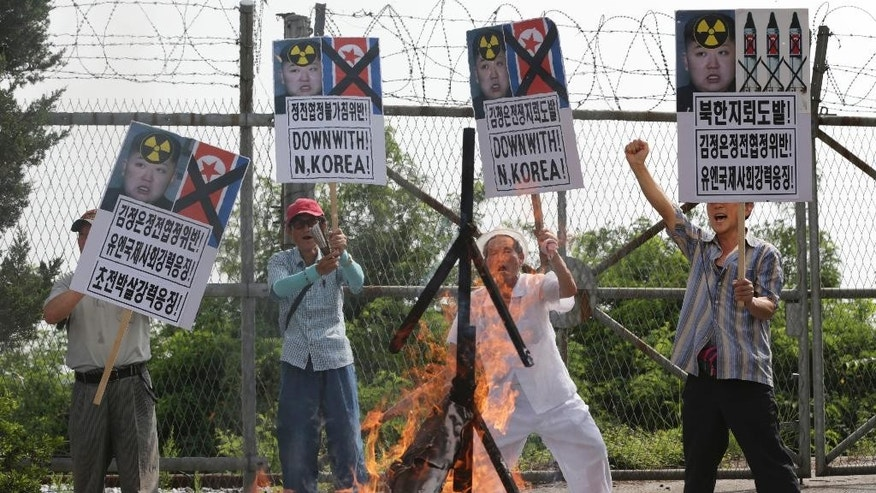 "FILE - In this Aug. 11, 2015, file photo, members of South Korean conservative group shout slogans after burning an effigy of North Korean leader Kim Jong Un and North Korean flags during a rally denouncing the North Korea at the Imjingak Pavilion near the border village of Panmunjom in Paju, South Korea. North Korea on Saturday, Aug. 15, 2015, threatened to attack South Korean loudspeakers that are broadcasting anti-Pyongyang propaganda messages across their shared border, the world's most heavily armed. The warning follows Pyongyang's earlier denial that it had planted land mines on the South Korean side of the Demilitarized Zone that injured two South Korean soldiers last week. Seoul retaliated for those injuries by restarting the loudspeaker propaganda broadcasts for the first time in 11 years and suggested more actions could follow. The placards read: ""North Korea, land mine provocation."" (AP Photo/Lee Jin-man, File)"