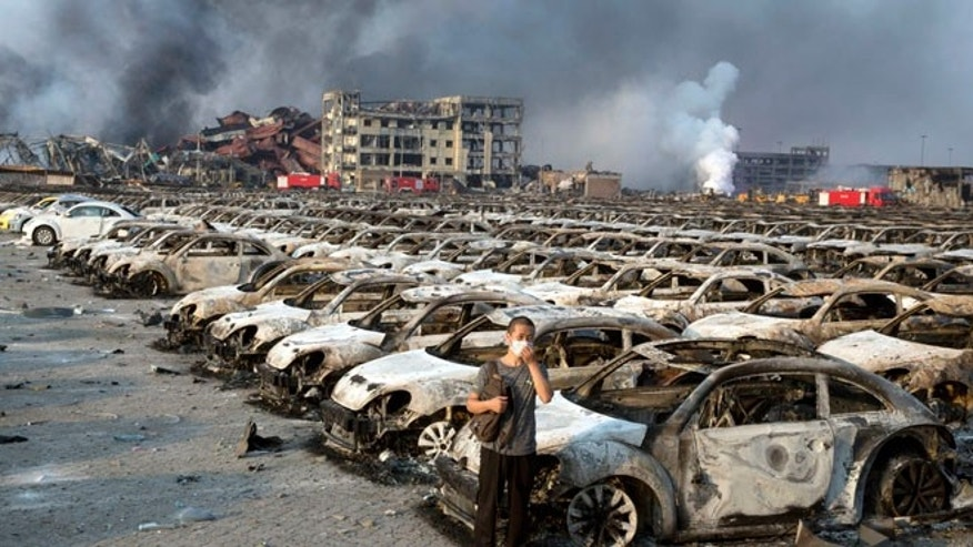 Aug. 13, 2015: A man stands near the charred remains of new cars at a parking lot near the site of an explosion at a warehouse in northeastern China's Tianjin municipality.mid potentially dangerous chemicals.
