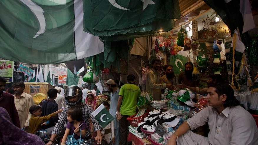 A Pakistani vendor waits for customers to sell national flags, caps and masks to celebrate the country's upcoming 69th Independence Day in Rawalpindi, Pakistan, Thursday, Aug. 13, 2015. Millions of Pakistanis will hold rallies for Independence Day on Friday to commemorate its independence in 1947 from British colonial rule. (AP Photo/B.K. Bangash)