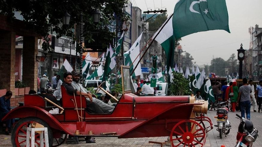 People celebrate the country's upcoming 69th Independence Day in Rawalpindi, Pakistan, Thursday, Aug. 13, 2015. Millions of Pakistanis will hold rallies for Independence Day on Friday to commemorate its independence in 1947 from British colonial rule.(AP Photo/B.K. Bangash)
