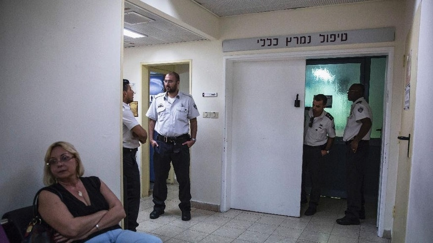 In this Monday Aug. 10, 2015 photo, shows Israeli Prisons Service guards secure the entrance to the intensive care unit were Mohammed Allan, a Palestinian prisoner on hunger strike is held in Barzilai hospital at the costal city of Ashkelon, Israel. Israel passed a law to force feed hunger strikers by a slim margin in July and elicited harsh criticism. Critics call force-feeding an unethical violation of patient autonomy and akin to torture. The Israeli Medical Association, which has urged physicians not to cooperate, is challenging the law in the Supreme Court. (AP Photo/Tsafrir Abayov)