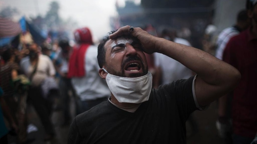 FILE - In this Wednesday, Aug. 14, 2013, file photo, a supporter of ousted Egyptian President Mohammed Morsi reacts during clashes with Egyptian security forces in Rabaah el-Adawiyah sit in, in Cairo's Nasr City district, Egypt. International rights groups are criticizing the Egyptian government for failing to hold officials accountable two years after one of the deadliest dispersals of protesters in the country's history. (AP Photo/Manu Brabo, File)