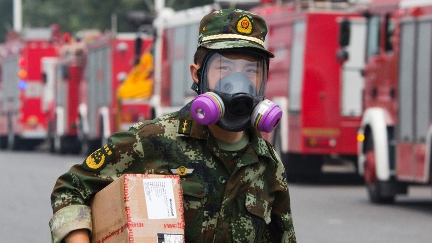 A Chinese firefighter walks near fire trucks near the site of an explosion in northeastern China's Tianjin municipality Saturday, Aug. 15, 2015. New explosions and fire rocked the Chinese port city of Tianjin on Saturday, where one survivor was pulled out and authorities ordered evacuations within a 3-kilometer (1.8-mile) radius to clean up chemical contamination. (AP Photo/Ng Han Guan)