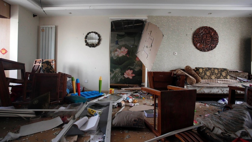 Aug. 14, 2015: Broken furnitures, windows and other items damaged by shock waves from explosions at a nearby port in northeastern China's Tianjin municipality are scattered in an apartment room.