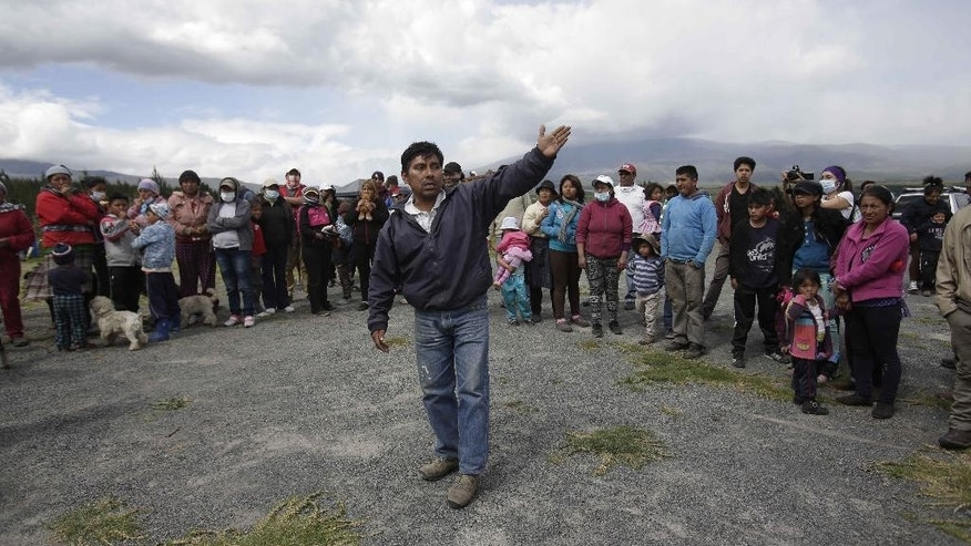 A village leader tries to quell fears of Santa Rita residents who set up camp alongside a road after a self-imposed evacuation from their homes, fearing a volcanic landslide from the nearby Cotopaxi volcano, pictured in background, in El Chasqui, Ecuador, Saturday, Aug. 15, 2015. Four blasts inside the volcano sent ash shooting into the sky Friday, coating highways, homes and cars just south of Ecuador's capital with a fine gray powder. Cotopaxi is considered one of the world's most dangerous volcanoes due to a glacial cover that makes it prone to fast-moving volcanic rock and mud flows, or lahares, and its proximity to a heavily populated area. (AP Photo/Dolores Ochoa)