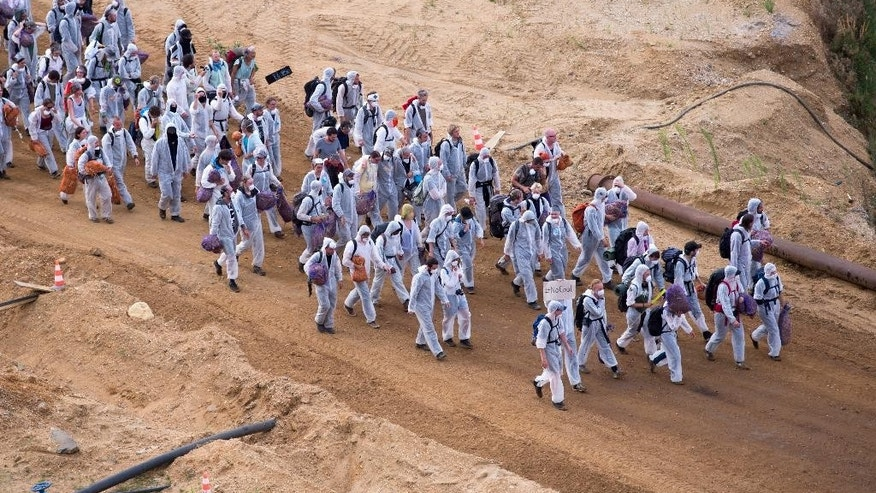 Protestors arrive for a demonstration  at the open-pit coal mine near Garzweiler, western Germany Saturday Aug. 15, 2015.  Several hundred environmental activists have stormed a lignite mine in western Germany to protest against the use of coal for electricity production.   ( Marius Becker/dpa via AP)