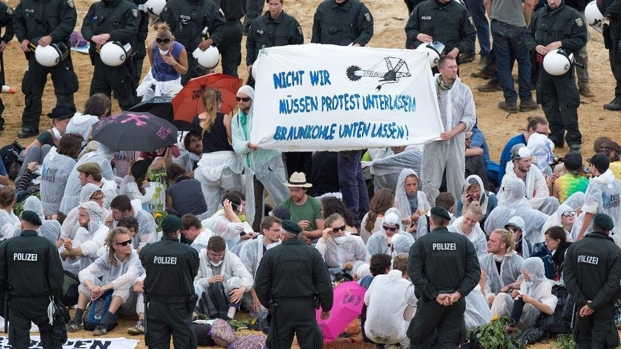Demonstrators stage a protest at the open-pit coal mine near Garzweiler, western Germany Saturday Aug. 15, 2015. Banner reads: We do not have to stop protests. leave the coal underground. Several hundred environmental activists have stormed a lignite mine in western Germany to protest against the use of coal for electricity production.  ( Marius Becker/dpa via AP)