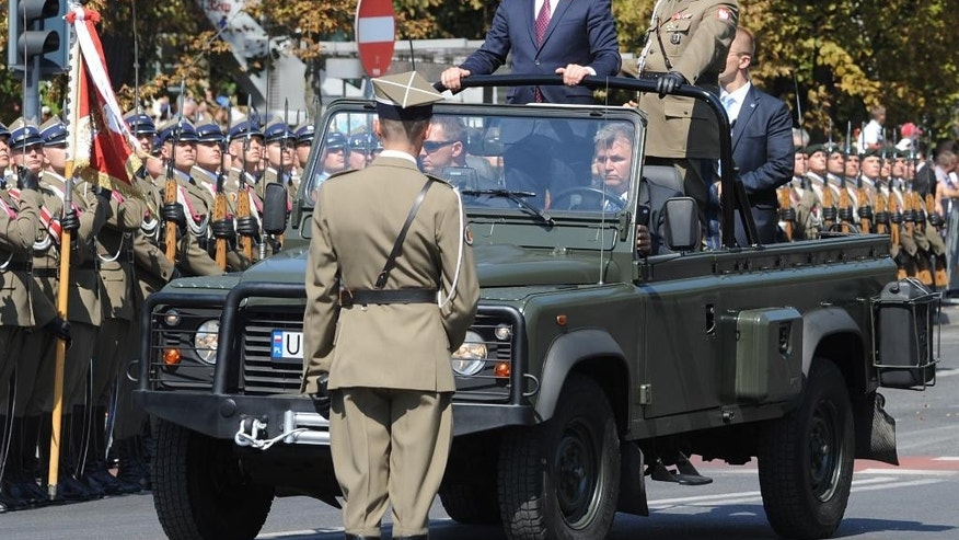 Polish President Andrzej Duda, center, reviews troops prior to a military parade celebrating the Polish Army Day in Warsaw, Poland, Saturday, Aug. 15, 2015. (AP Photo/Alik Keplicz)
