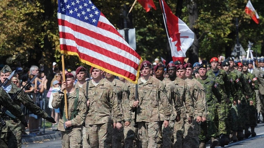 Soldiers from the U.S. and Canada currently training in Poland march during a military parade celebrating the Polish Army Day in Warsaw, Poland, Saturday, Aug. 15, 2015. (AP Photo/Alik Keplicz)