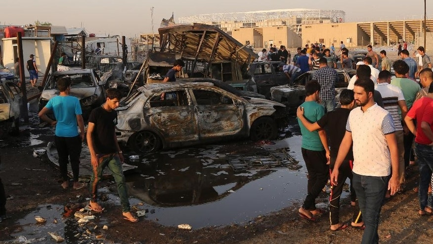 People gather at the scene of a deadly car bomb in the Habibiya neighborhood of Sadr City, Baghdad,  Iraq, Saturday, Aug. 15, 2015. An Iraqi police official says the explosion at a popular car dealership in eastern Baghdad, that has been targeted multiple times in the past, has killed at least eight and wounded over a dozen people. (AP Photo/Karim Kadim)