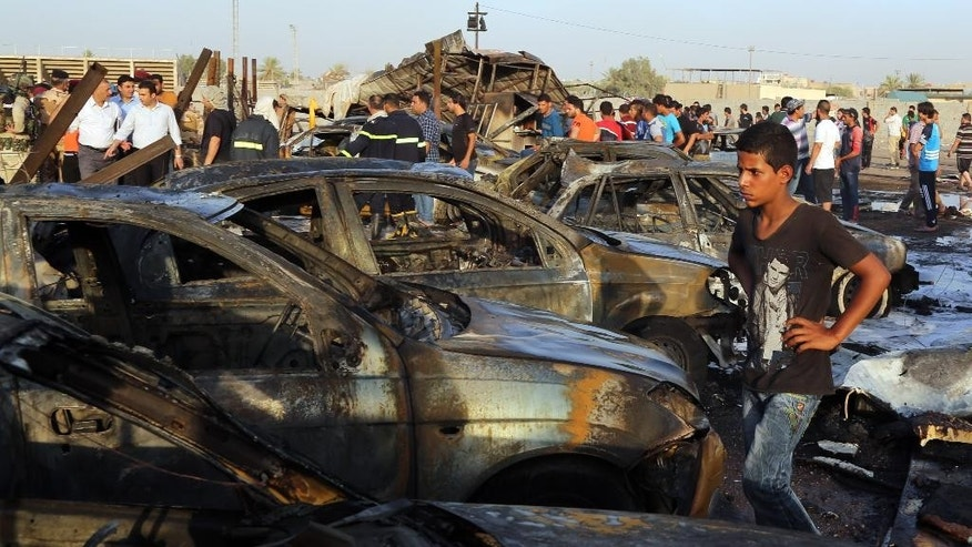 Civilians gather at the scene of a deadly car bomb in the Habibiya neighborhood of Sadr City, Baghdad, Iraq, Saturday, Aug. 15, 2015. An Iraqi police official says the explosion at a popular car dealership in eastern Baghdad, that has been targeted multiple times in the past, has killed at least eight and wounded over a dozen people. (AP Photo/Karim Kadim)