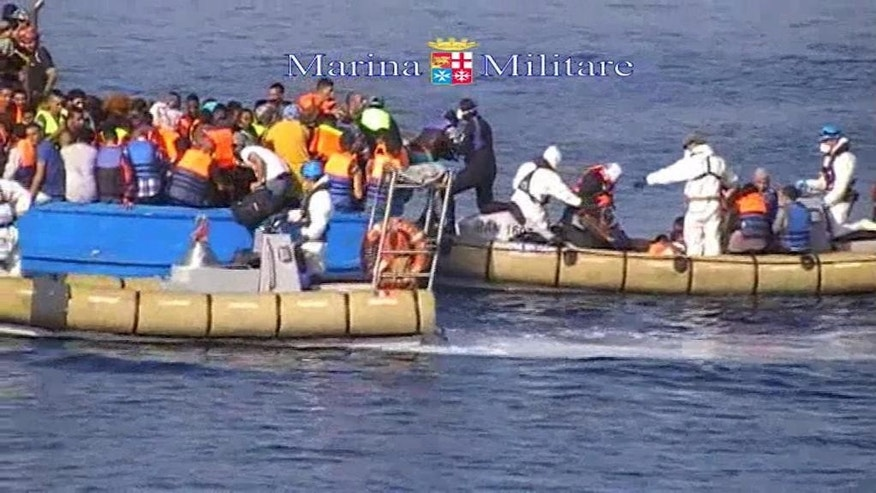 This image taken from video provided by the Italian Navy (Marina Militare) Saturday, Aug. 15, 2015, shows an Italian Navy RIB approaching a fishing boat crowded with migrants off the coast of Libya. At least 40 migrants died on Saturday in the hold of an overcrowded smuggling boat in the Mediterranean Sea north of Libya, apparently killed by fuel fumes. Some 320 others on the same boat were saved by the Italian navy, the rescue ship's commander said. Migrants by the tens of thousands are braving the perilous journey across the Mediterranean this year, hoping to reach Europe and be granted asylum. (Marina Militare via AP)