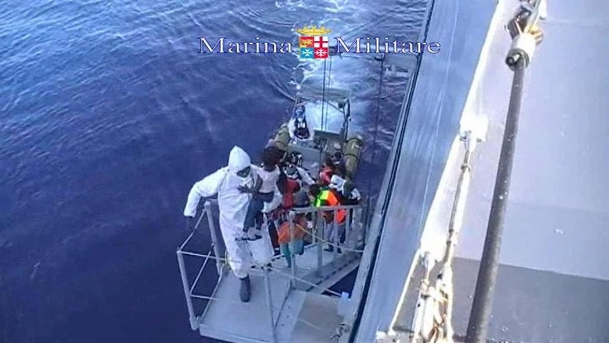 This image taken from video provided by the Italian Navy (Marina Militare) Saturday, Aug. 15, 2015, shows migrants boarding a navy vessel after being rescued from a fishing boat, off the coast of Libya. At least 40 migrants died on Saturday in the hold of an overcrowded smuggling boat in the Mediterranean Sea north of Libya, apparently killed by fuel fumes. Some 320 others on the same boat were saved by the Italian navy, the rescue ship's commander said. Migrants by the tens of thousands are braving the perilous journey across the Mediterranean this year, hoping to reach Europe and be granted asylum. (Marina Militare via AP)