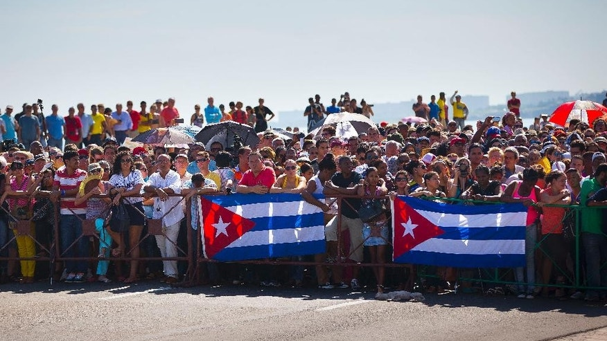 Cubans stand along the Malecon, the avenue that runs along the seawall at the northern shore of Havana, during Secretary of State John Kerry's remarks for the raising of the U.S. flag over the newly reopened embassy in Havana, Cuba. Friday, Aug. 14, 2015. Kerry traveled to the Cuban capital to raise the U.S. flag and formally reopen the long-closed U.S. Embassy. Cuba and U.S. officially restored diplomatic relations July 20, as part of efforts to normalize ties between the former Cold War foes. (AP Photo/Pablo Martinez Monsivais,Pool)