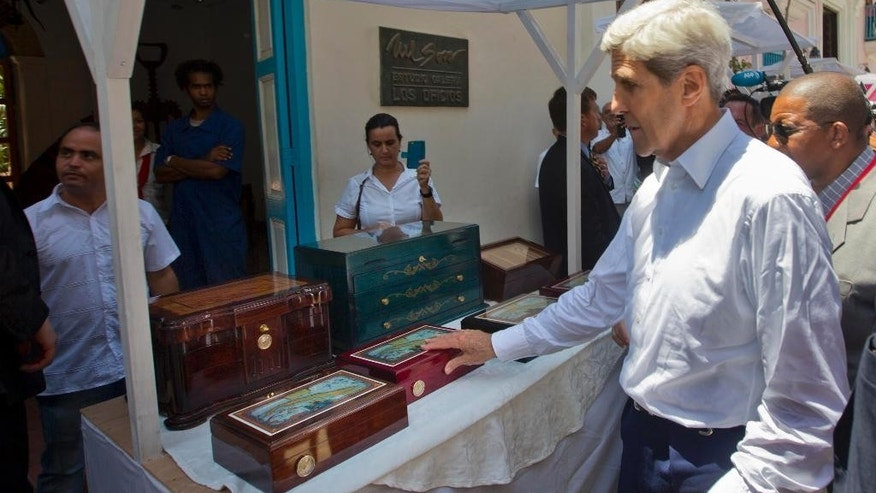 Secretary of State John Kerry stops to buy a humidor from a local vendor during his visit to the Plaza de San Francisco in Old Havana, Cuba, Friday, Aug. 14, 2015. Kerry traveled to the Cuban capital to raise the U.S. flag and formally reopen the long-closed U.S. Embassy. Cuba and U.S. officially restored diplomatic relations July 20, as part of efforts to normalize ties between the former Cold War foes. (AP Photo/Pablo Martinez Monsivais,Pool)