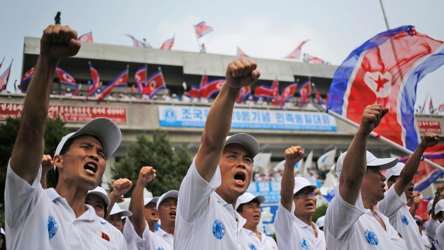 Participants raise their fists as they chant slogans during a reunification rally in the border village of Panmunjom at the DMZ in North Korea, Saturday, Aug. 15, 2015. Though staged to mark the 70th anniversary of Japanese World War II defeat, the rally came just after Pyongyang said the south had committed an act of war by broadcasting anti-North Korea propaganda across the border. (AP Photo/Dita Alangkara)