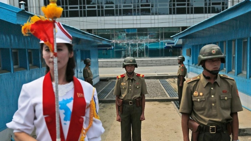 North Korean soldiers stand guard as a band member performs during a reunification rally in the border village of Panmunjom at the DMZ in North Korea, Saturday, Aug. 15, 2015. Though staged to mark the 70th anniversary of Japanese World War II defeat, the rally came just after Pyongyang said the south had committed an act of war by broadcasting anti-North Korea propaganda across the border. (AP Photo/Dita Alangkara)