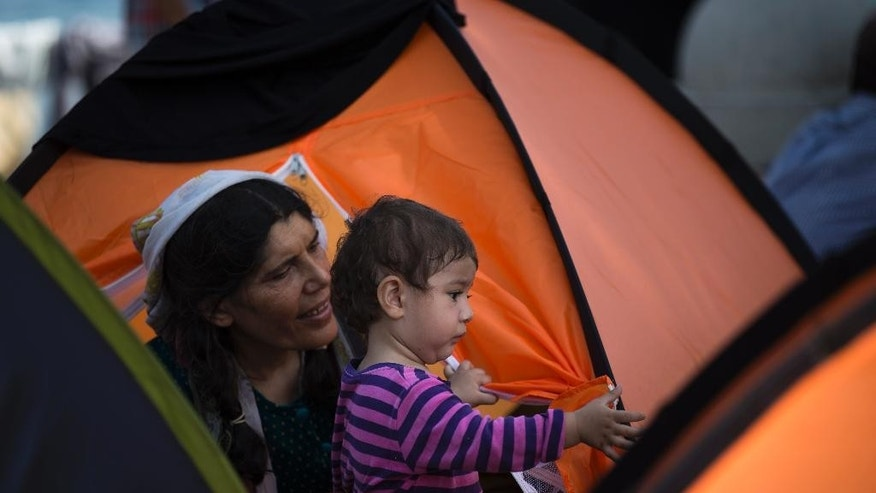 A woman with her child rests at a tent camp as other migrants gather at a makeshift migrant detention center at Kos' abandoned football stadium after crossing from Turkey, at the southeastern island of Kos, Greece, Friday, Aug. 14, 2015. On Friday, the International Organization for Migration said the number of migrants and asylum-seekers who have crossed the Mediterranean to Europe this year will pass the quarter-million mark by the end of the month — more than half of them arriving in Greece. (AP Photo/Alexander Zemlianichenko)