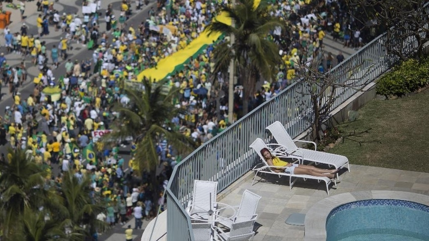 A woman sleeps in a residential penthouse while thousands below march in an anti-government protest demanding the impeachment of Brazil's President Dilma Rousseff, in at Copacabana beach, Rio de Janeiro, Brazil, Sunday, Aug. 16, 2015. Demonstrators are taking to the streets across Brazil for a day of nationwide anti-government protests. President Rousseff's second term in office has been shaken by a snowballing corruption scandal involving politicians from her Workers' Party, as well as a spluttering economy, spiraling currency and rising inflation, making her popularity ratings fall to historic lows. (AP Photo/Leo Correa)