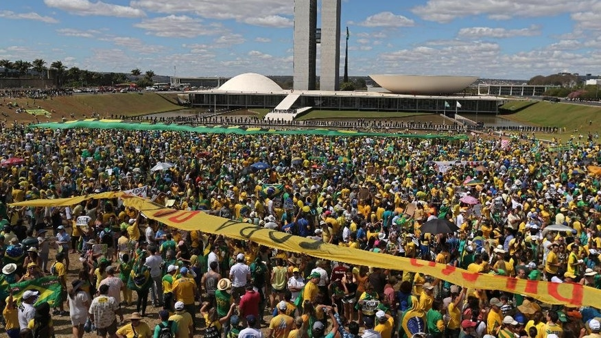 "Carrying banners that read in Portuguese ""Dilma Out"" and ""Impeachment Now,"" thousands of demonstrators take part in a protest against the government of Brazil's President Dilma Rousseff, in front of the Brazilian National Congress, in Brasilia, Brazil, Sunday, Aug. 16, 2015. Demonstrators are taking to the streets across Brazil for a day of nationwide anti-government protests. President Rousseff's second term in office has been shaken by a snowballing corruption scandal involving politicians from her Workers' Party, as well as a spluttering economy, spiraling currency and rising inflation, making her popularity ratings fall to historic lows. (AP Photo/Eraldo Peres)"