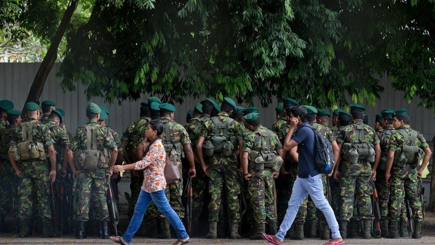 Sri Lank's elite police force members gather outside a polling material distribution center in Colombo, Sri Lanka, Sunday, Aug. 16, 2015. The island nation holds parliamentary elections on August 17, 2015. (AP Photo/Gemunu Amarasinghe)